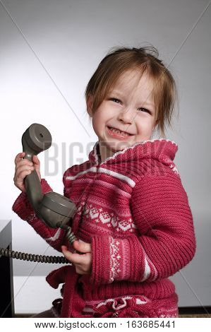 photo of little girl using old phone