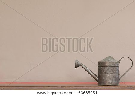 close up vintage style watering can on shelf with brown wall background