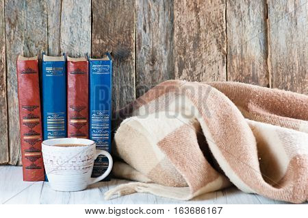 a pile of old books on a wooden retro background and a white worktop