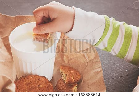 a Children handle dunks cookies in milk