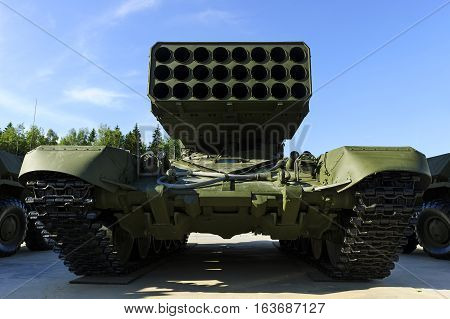 Multiple missile launcher, military industry, heavy mobile flamethrower system among two armored personnel carriers, green thermobaric ballistic weapon complex, modern army, blue sky on background
