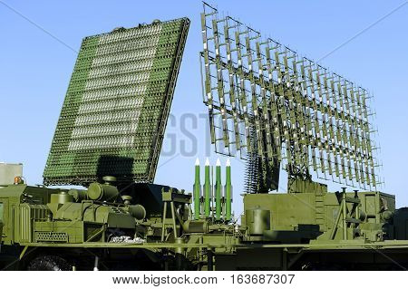 Air defense radars of military mobile antiaircraft systems in green color and ballistic rocket launcher with four cruise missiles in centre of frame, modern army industry