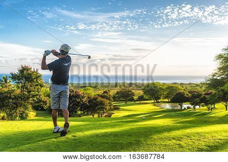 Golfer teeing off on an elevated par 3 tee box, hitting ball towards ocean
