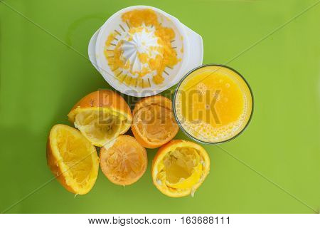 Glass of fresh squeezed orange juice with squeezer and orange leftovers