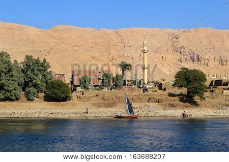 Nile River Egypt - February 3 2016: People on a boat with Village along the shore showing life along the Nile River in Egypt Africa