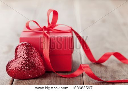 Gift or present box with red bow ribbon and glitter heart on wooden table for Valentines day.