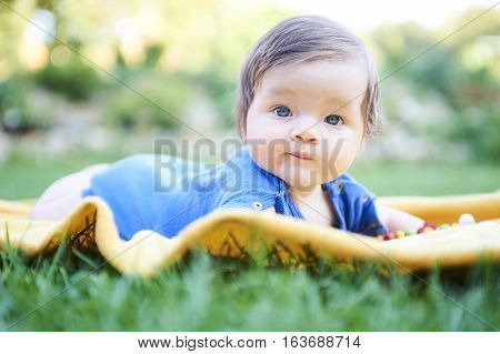 Newborn cute girl with blue eyes in the beautiful park outdoors, lies on a blanket and looking into camera