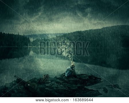 Young boy artist with a guitar and books sit down on a rocky shore near the lake and forest. Bad mood hard thinking no inspiration concept with his head fired and the smoke rising up.