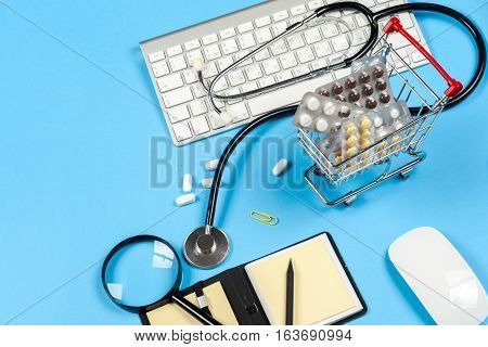 Shopping trolley with pills and medicine - medical concept. Medical report with pills and a stethoscope.