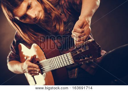 Man Is Tuning The Guitar.
