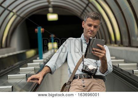Man With Tablet On The Escalator