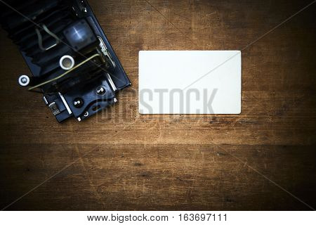 Vintage photo film camera with blank photo frame on a scratched old wooden table. Focused to paper frame.