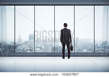 Back view of businessman with briefcase in modern interior with city view looking into the distance. Research concept. 3D Rendering