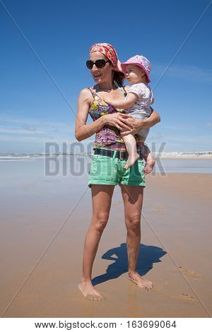 Mum With Baby Looking At Beach