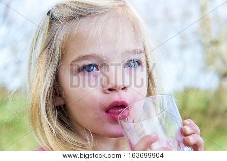 Girl holding glass drinking lemonade. Happy child at summer