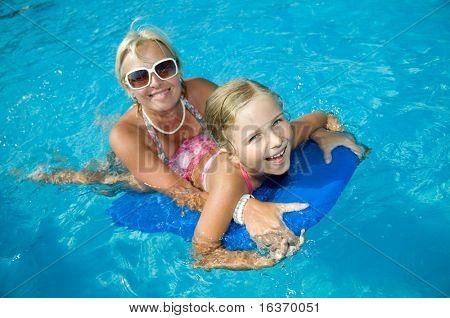 Boldog nyaralás - kislány, anya, kék vízben beszállás