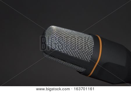 New modern microphone recording device on black background. Electronic equipment for singer.