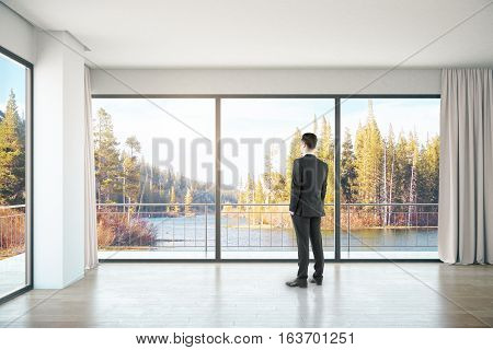 Businessman in unfurnished concrete interior with panoramic windows and landscape view. 3D Rendering