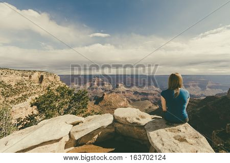 A woman sitting down overlooking the beautiful view at the Grand Canyon