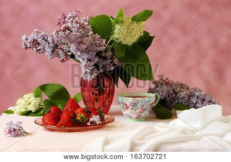 Lilac, strawberries and tea on white table still life.