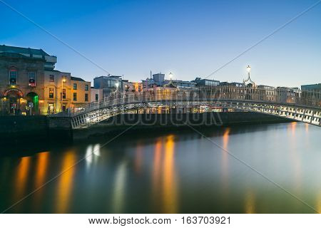 Dublin, Ireland - 2 Jan 2017: Evening view of famous Ha'penny Bridge in Dublin, Ireland at sunset