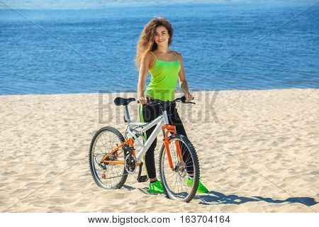 Girl athlete with long curly hair wearing black sweat pants and a light green T-shirt to go with the bike in the morning on the shore near the ocean.