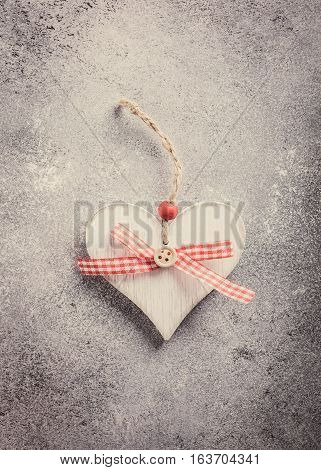 Valentines Day greeting card with decorative wooden heart on concrete stone with copy space for text. Valentine's Day concept. View from above. Toned.
