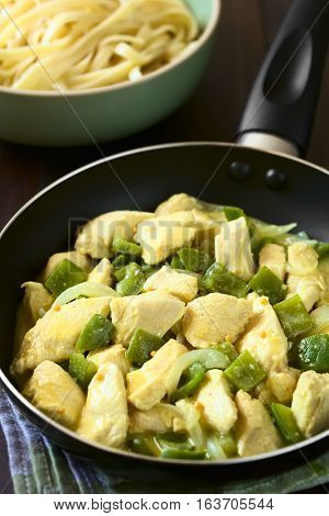 Chicken with green bell pepper and onion in mustard cream sauce in frying pan photographed with natural light (Selective Focus Focus in the middle of the dish in the pan)