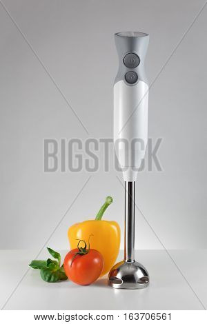 Small electric blender and fresh vegetables, symbol of healthy eating, healthy cooking, home preparation vegetables