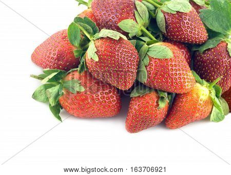 Heap of ripe appetizing red strawberry fruits with green leaves isolated on white closeup
