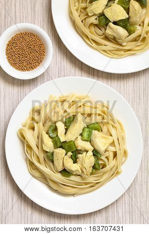 Chicken with green bell pepper and onion in mustard cream sauce on fettuccine pasta served on plates raw mustard seeds in small bowl on the side photographed overhead with natural light