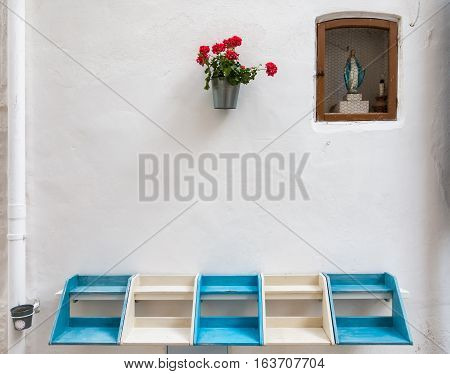 Shrine or street altar with a small statue of the virgin Mary flowers and a blue and white bench in the white city Ostuni in Puglia Italy.