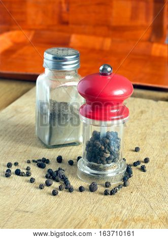 Still life with black peppercorn, hand mills with red cap and glass spice jar on kitchen table. Photo closeup