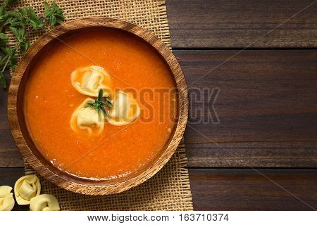 Homemade fresh cream of tomato soup with tortellini garnished with fresh oregano served in wooden bowl photographed overhead on dark wood with natural light (Selective Focus Focus on the top of the soup)