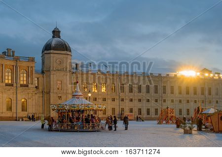 Gatchina, Russia - January 2, 2017: Gatchina Palace, New Year's Fair on the parade ground. Children's carousel at the fair. Photo taken in the evening.