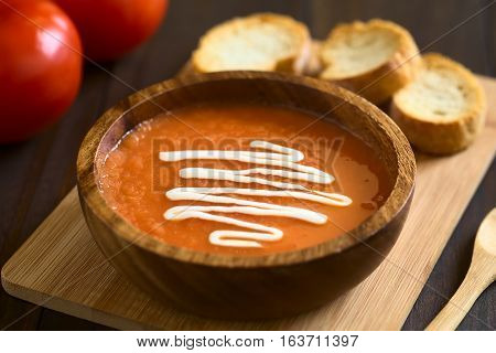 Homemade fresh cream of tomato soup served in wooden bowl with toasted bread on wooden board photographed with natural light (Selective Focus Focus in the middle of the soup)