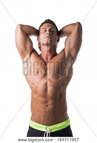 Handsome shirtless bodybuilder with eyes closed and hands behind head, isolated on white background
