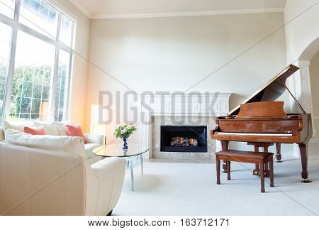 Bright day light coming into living room with burning fireplace grand piano and white leather sofa.