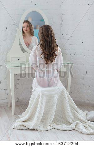 Gentle beautiful young woman in white lingerie with a robe sits behind the night table in front of the mirror and preening.