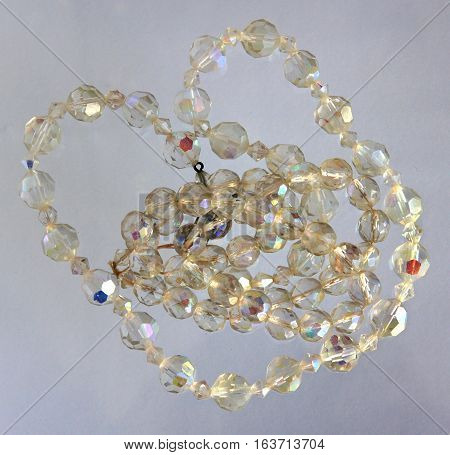 Necklaces of glass beads and pearls on white background