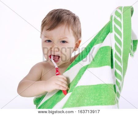 little boy brushing his teeth on white