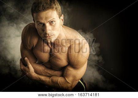 Handsome shirtless bodybuilder shot from above, standing on dark smoky background