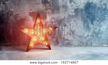 Large decorative retro star with lots of burning lights on grunge concrete background. Beautiful decor, modern design element. The loft style studio