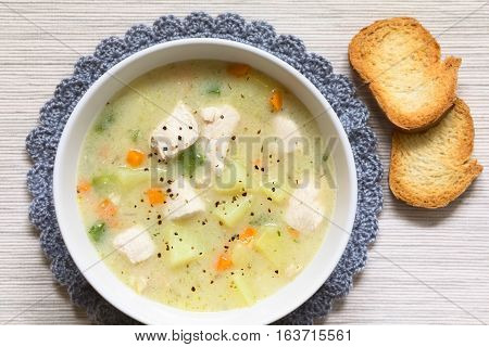 Chicken and potato chowder soup with green bell pepper and carrot in bowl with toasted bread slices on the side photographed overhead with natural light (Selective Focus Focus on the top of the soup)