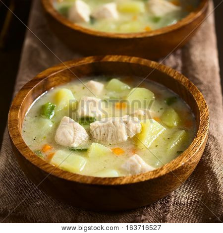 Chicken and potato chowder soup with green bell pepper and carrot in wooden bowls photographed on dark wood with natural light (Selective Focus Focus in the middle of the soup)