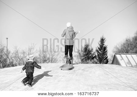 A toddler girl and her teenage sister having fun sliding down a hill in winter in black and white