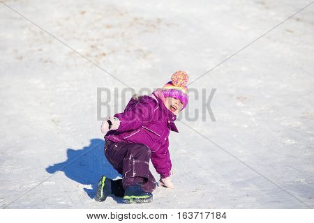 Four year old happy girl sliding downhill on a winter hill