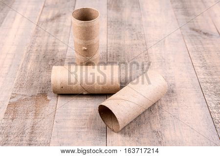 Three Empty Toilet Paper Rolls Isolated On A Wood Background