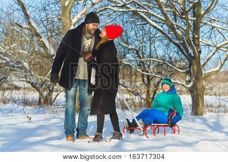 Happy family having fun snowy woodland outdoor.