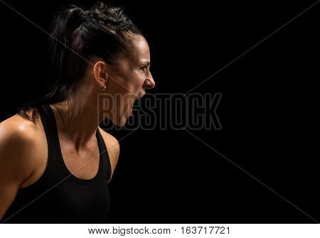 Mad furious young woman screaming over black background